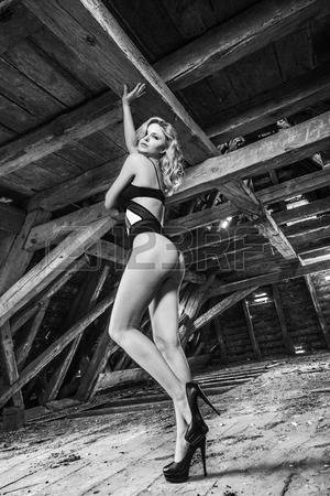 60681716-bottom-view-of-blonde-sensual-woman-posing-in-old-wooden-attic-of-abandoned-building-wearing-black-s